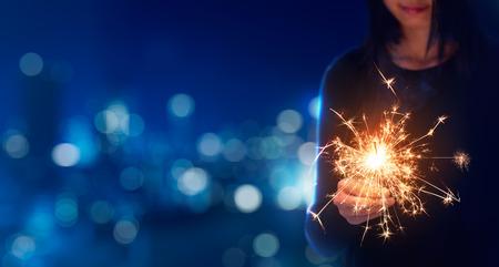 Female playing sparklers during celebration - Bokeh Background