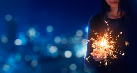Female playing sparklers during celebration - Bokeh Background