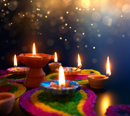 Diya lamps lit on colorful rangoli during diwali celebration 스톡 콘텐츠 - 102625575