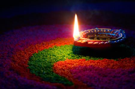 Happy Diwali - Diya lamp on top of colorful rangoli