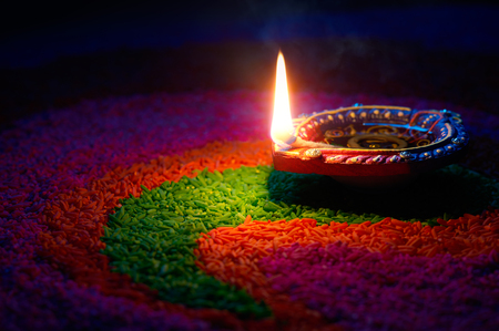Happy Diwali - Diya lamp on top of colorful rangoli