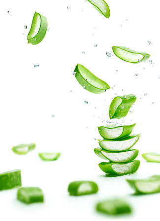 Aloe Vera slices stacked with water splash over white