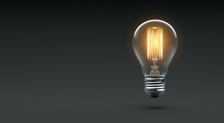 Glowing Edison light bulb on dark Stockfoto