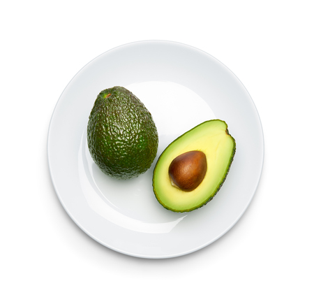 Avocado on plate over white