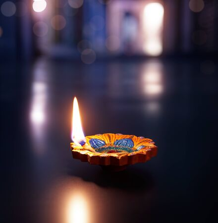 Happy Diwali - Lit diya lamp on an abstract background with shallow depth of field