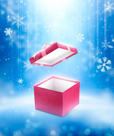 Red open gift box on fallen defocused snowflakes background