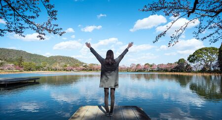 Young woman enjoying freedom with open hands in front of lake with nature landscape during spring time   Banco de Imagens