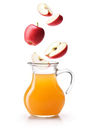 Apples dropping on a jug of apple cider vinegar, isolated on white background