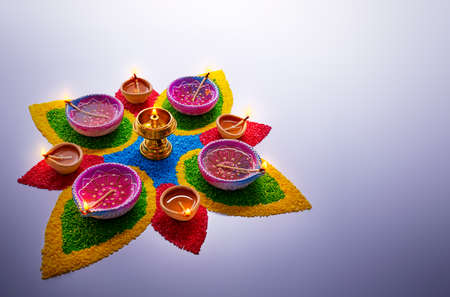 Happy Diwali, diya lamps lit on colorful rangoli with copy space
