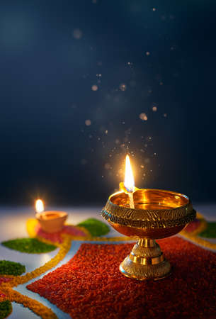 Happy Diwali, Glittering diya oil lamp against dark background with copy space
