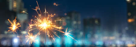 Happy New Year, Sparkler with blurred city light background