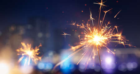 Happy New Year, Glittering burning sparkler against blurred city light background