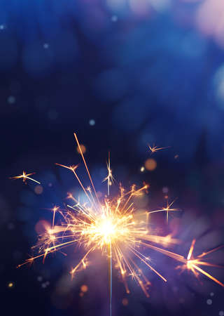 Glittering burning sparkler against fireworks background with copy space Zdjęcie Seryjne