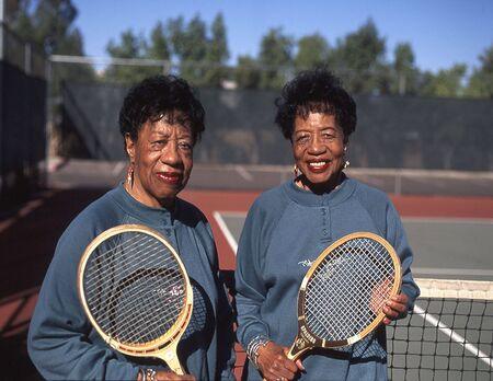 Senior citizen twins holding tennis racquets