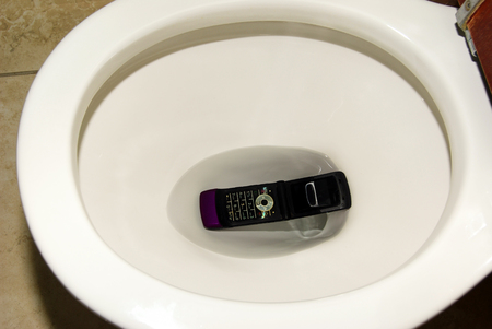 toilet bowl: A cell phone accidentally dropped in a toilet bowl