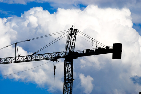 monsoon clouds: Construction crane silhouetted against a blue sky with monsoon clouds