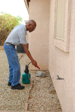 exterminating: Male senior citizen using a do-it-yourself  pest control kit to spray the side of his house in the backyard