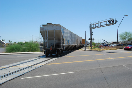 railroad crossing: Freight train passing through a railroad crossing in Mesa, AZ
