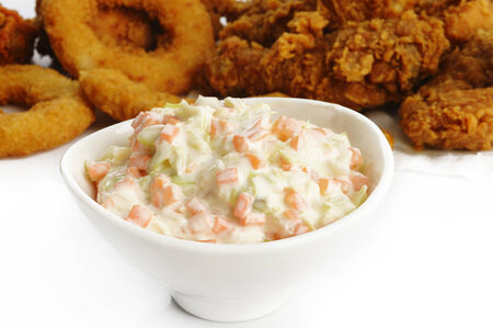 Coleslaw salad in bowl and fried food photo