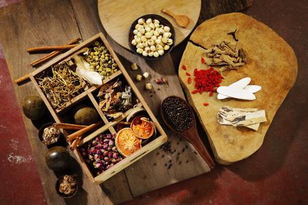 La medicina herbal china y té de la flor en la madera Foto de archivo