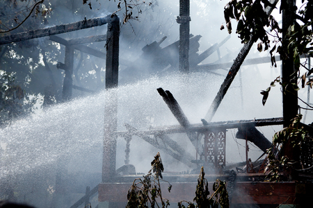smoldering: Smoldering remains of a wooden house with a fireman spraying water firefighters extinguish a fire in a wooden house