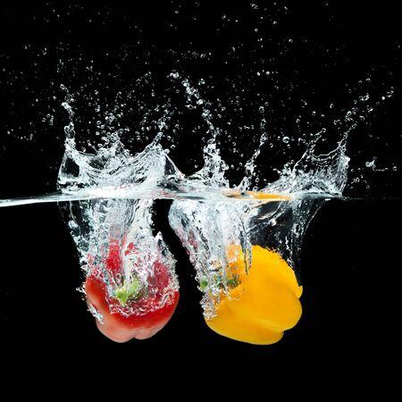 Fresh paprika or sweet pepper splash in water on black background photo