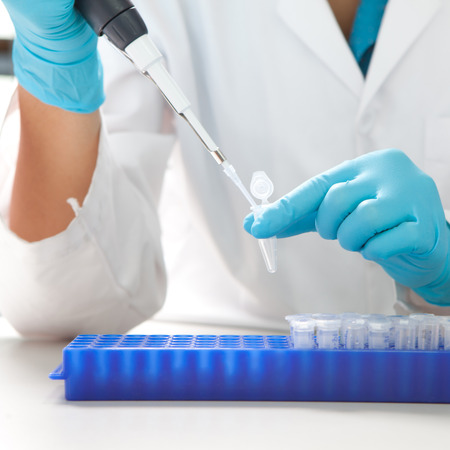 Laboratory micro pipette drops the biological solution in eppendorf Stock Photo
