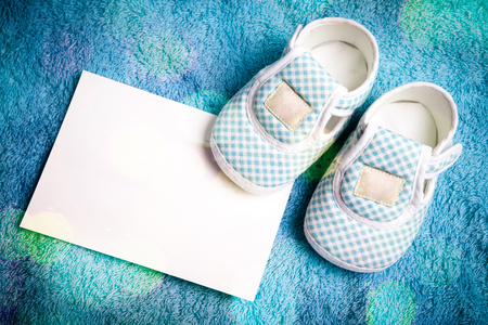 Whiteblue baby shoe with blank note or paper to write some text photo