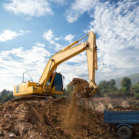 dumper truck: Excavator loading dumper truck tipper in construction site Stock Photo