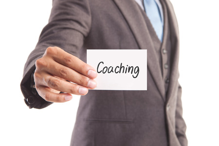 Businessman hand showing someone his business card withCoaching message Stock Photo