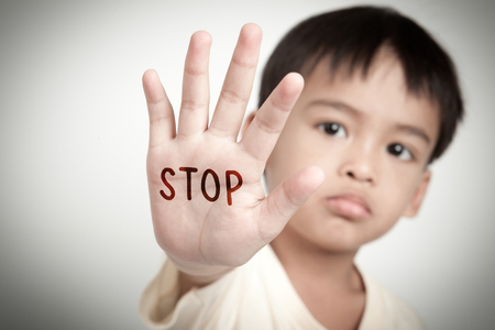 sad face of asian kid and hand raise stop written on his hand.