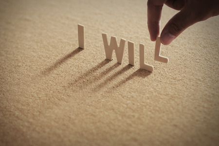 I WILL wood word on compressed board,corkboard with humans finger at L letter