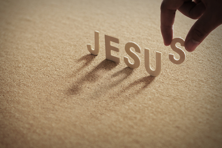 JESUS wood word on compressed board with humans finger at S letter