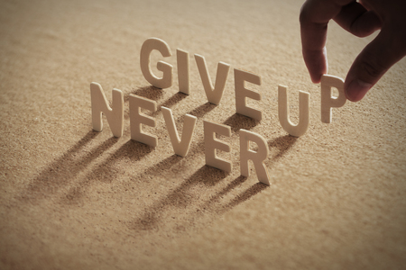 NEVER GIVE UP wood word on compressed board with human's finger at P letter Archivio Fotografico