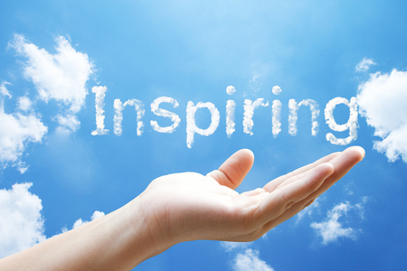 """high sea: """"inspiring"""" cloud word floating on upturned hands. Stock Photo"""