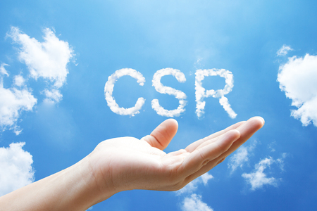 """""""CSR(Corporate Social Responsibility)"""" cloud word floating on upturned hands."""