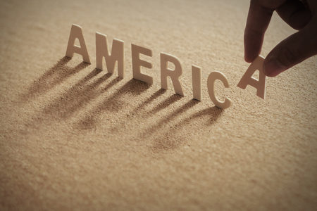 AMERICA wood word on compressed or corkboard with human's finger at A letter. Standard-Bild