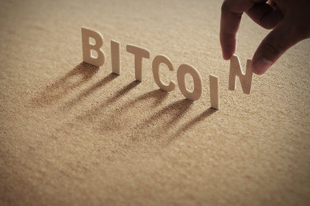 BITCOIN wood word on compressed or corkboard with human's finger at N letter.