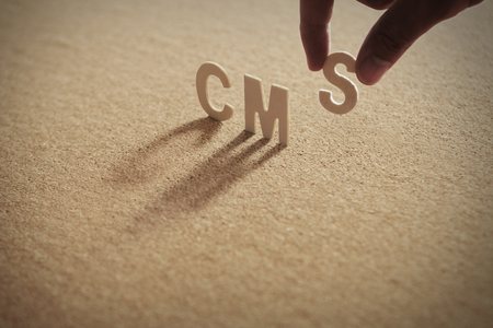CMS wood word on compressed or corkboard with human's finger at S letter. Standard-Bild