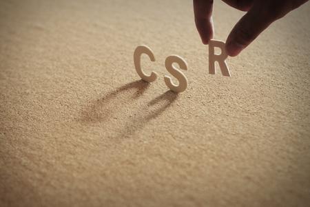 CSR-Holzwort auf komprimiertem oder Pinnwand mit menschlichem Finger am R-Buchstaben. Standard-Bild