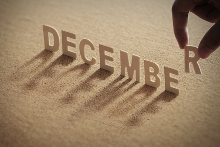 DECEMBER wood word on compressed or corkboard with human's finger at R letter. Standard-Bild
