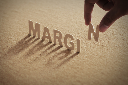 MARGIN wood word on compressed or corkboard with human's finger at N letter.
