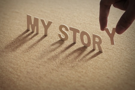 MY STORY wood word on compressed or corkboard with human's finger at Y letter. Standard-Bild
