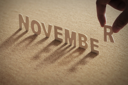 NOVEMBER wood word on compressed or corkboard with human's finger at R letter. Standard-Bild