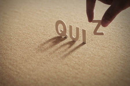 QUIZ wood word on compressed or corkboard with human's finger at Z letter. Standard-Bild