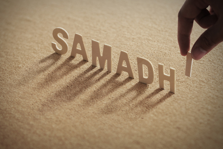 SAMADHI wood word on compressed or corkboard with human's finger at I letter. Standard-Bild