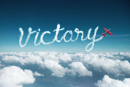 victory word created from a trail of smoke by Acrobatic plane.