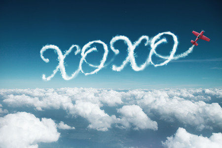 XOXO word created from a trail of smoke by Acrobatic plane.