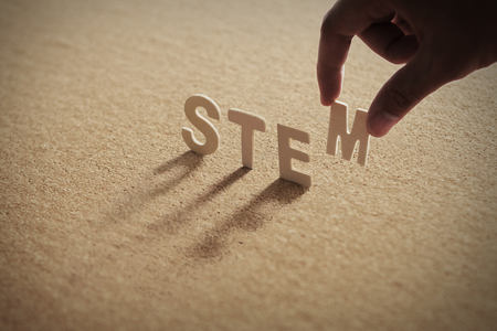 STEM wood word on compressed or corkboard with human's finger at T letter.