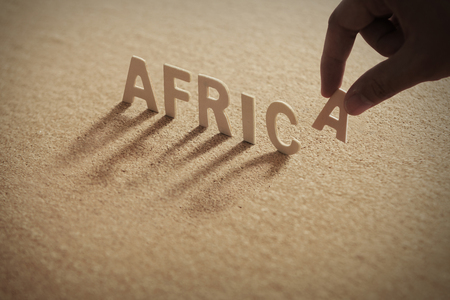 AFRICA wood word on compressed or corkboard with humans finger at A letter.